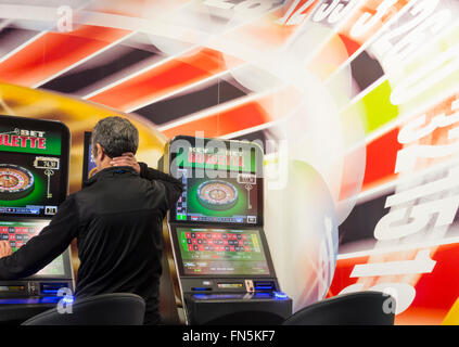 Mature man using fixed odds Roulette machine in Bookmakers. England, UK - Stock Photo