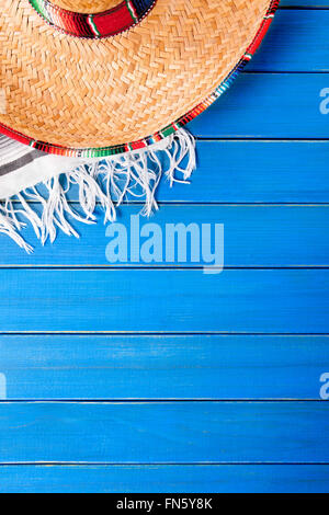Mexican sombrero with traditional serape blanket laid on an old blue painted pine wood floor.  Space for copy. - Stock Photo