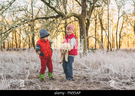 Two boys carrying golden retriever puppy dog - Stock Photo