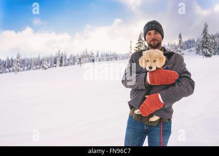 Man holding golden retriever puppy dog in his coat - Stock Photo