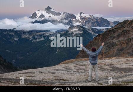 Man standing with arms raised, Mount Shuksan, Washington, America, USA - Stock Photo