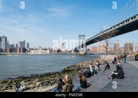 People sitting on the steps in DUMBO, Brooklyn, near the Manhattan Bridge looking across the East River to Manhattan, - Stock Photo