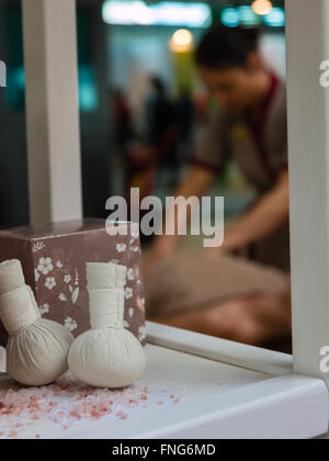 Spa Setting with Bath Salt and Cotton Bag for Thai Massage, Masseuse doing Massage in background - Stock Photo