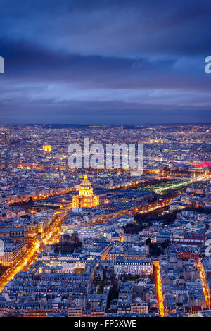 Aerial view of Paris at twilight with the Invalides and Army Museum at center and the Arc of Triumph in the distance. - Stock Photo