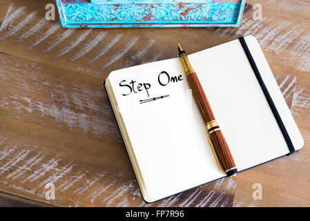 Retro effect and toned image of a fountain pen on a notebook. Handwritten text Step One as business concept image - Stock Photo