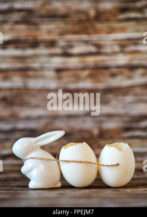 Conceptual White Easter Bunny Porcelain Pulling Two Broken Egg Shells Using a Small String on a Wooden Table with - Stock Photo