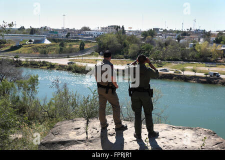 Border Patrol Agent and Texas Department of Public Safety officer observe activity in the city of Miguel Aleman. - Stock Photo
