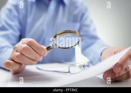 Businessman reading documents with magnifying glass - Stock Photo