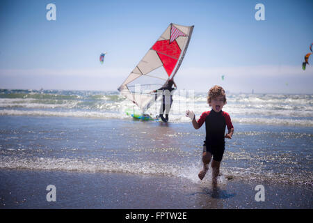 Small child running on the beach and father in the background, Viana do Castelo, Norte Region, Portugal - Stock Photo