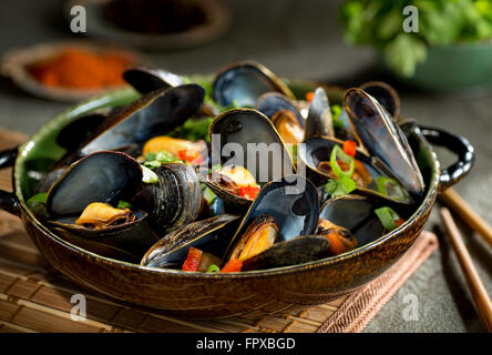 Delicious asian style steamed mussels with red pepper, green onion, and coriander in a coconut broth. - Stock Photo