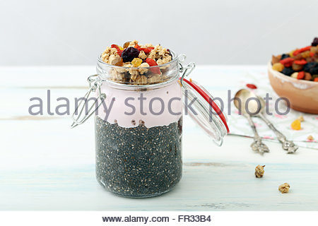 Healthy breakfast with chia seeds pudding, granola, fruits and berries in mason jar - Stock Photo