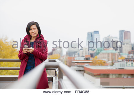 Middle-aged Asian woman using cell phone on rooftop - Stock Photo