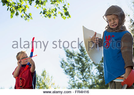 Young boys play fighting in costumes. - Stock Photo