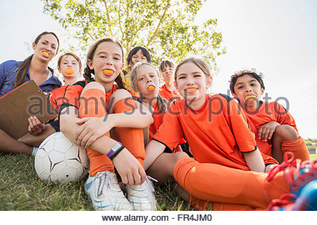 Girls soccer team smiling with oranges in their mouths. - Stock Photo