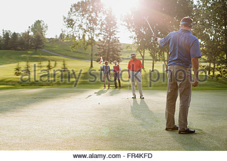 golfer lining up shot with putter - Stock Photo