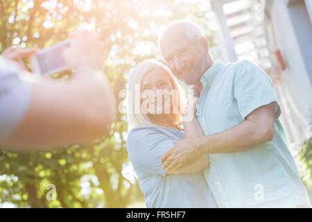 Man photographing senior couple outdoors - Stock Photo