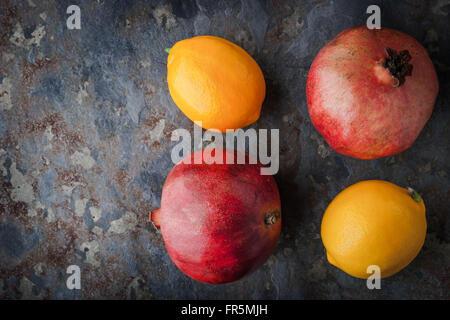 Lemons, pomegranates on the stone table horizontal - Stock Photo