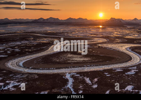 The sun sets behind the Wood River Mountains and Snake River within the Togiak National Wildlife Refuge, Alaska. - Stock Photo