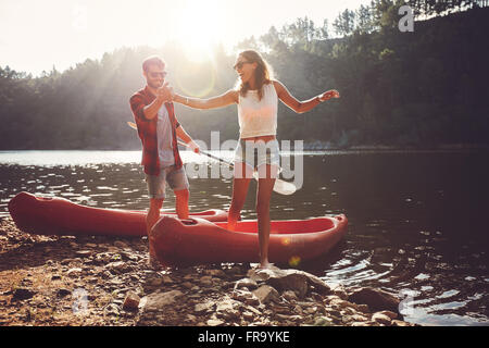 Young man helping woman to step out of a kayak. Couple after kayaking in the lake on a sunny day. - Stock Photo