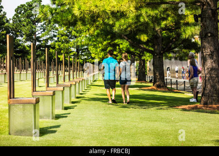 A couple strolls through the chairs honoring bombing victims at the Oklahoma City bombing memorial in Oklahoma City, - Stock Photo