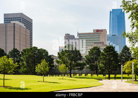The grounds of the Oklahoma City bombing memorial, showing the Field of Chairs and city buildings. Oklahoma, USA. - Stock Photo