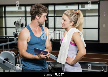 Trainer using a digital tablet while talking to a woman - Stock Photo