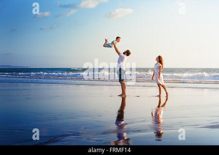 Happy family - father, mother, baby son walk with fun along edge of sunset sea surf on black sand beach. - Stock Photo