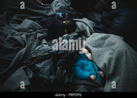 Idomeni refugee camp on Greek Macedonia border, waiting refugees at the checkpoint, a small child sleeps wrapped - Stock Photo