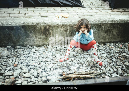 Idomeni refugee camp on Greek Macedonia border, a child sits on the platform at the station, Idomeni, Central Macedonia, - Stock Photo
