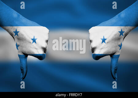 failure of Honduras - hands gesturing thumbs down in front of flag - Stock Photo
