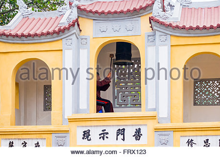 A novice monk rings a bell at One Pillar Pagoda temple complex, Hanoi, Vietnam - Stock Photo