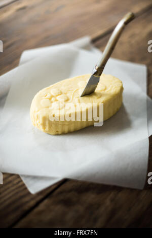 close up on a mound of rustic butter wrapped in paper with a knife, placed on a wooden table - Stock Photo
