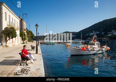 Woman sitting on a bench in the idyllic fishing village with fishing boat, Kioni, Ithaca, Ionian Islands, Greece - Stock Photo