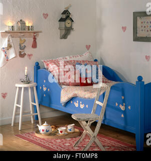 Colorful checked cushions on painted blue bed in child's bedroom with a wooden chair and stool - Stock Photo