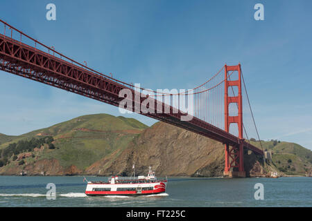 Leisure boat passing underneath the Golden Gate Bridge in San Francisco, California, USA - Stock Photo