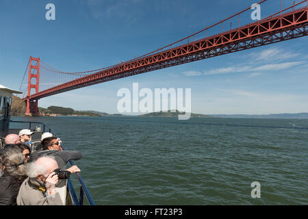 Passengers on a sightseeing boat underneath the Golden Gate Bridge in San Francisco, California, USA - Stock Photo