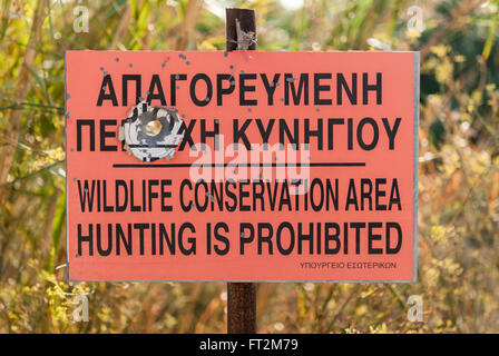 Hunting prohibited sign with bullet holes. Alaminos. Cyprus. - Stock Photo