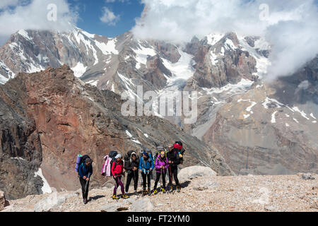 Backpackers Team Staying on Rocky Moraine - Stock Photo