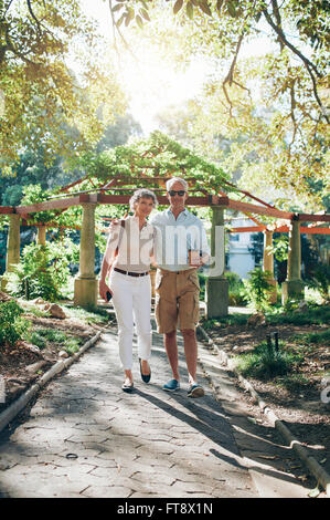 Full length portrait of loving senior couple walking through a park. Mature tourist walking in a city park. - Stock Photo