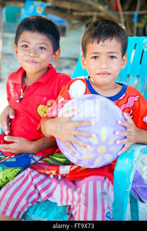 Two cute young Thai boys sit for a portrait on the Island of Koh Samet near Bangkok Thailand. - Stock Photo