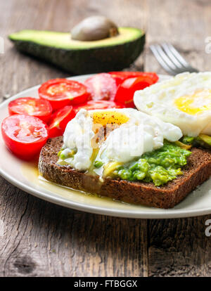 Open toast with avocado and egg, cherry tomatoes on a wooden background - Stock Photo