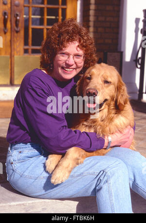 Outdoor portrait of middle-aged woman with her Golden Retriever dog - Stock Photo