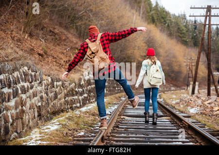 Back view of beautiful young couple with backpacks waking outdoors together - Stock Photo