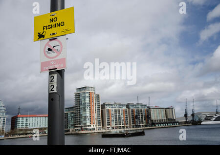 Signs on a lamppost at The Royal Victoria Dock stating that fishing and swimming are not allowed. - Stock Photo