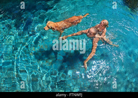Mother with little child on back play with fun and train golden labrador retriever puppy in swimming pool. - Stock Photo