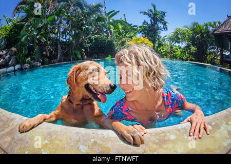 Funny portrait of smiley woman playing with fun and training golden retriever puppy in outdoor swimming pool. - Stock Photo