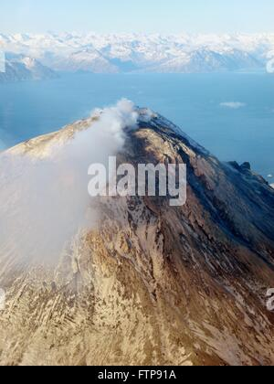 A steam plume rises from the snow-covered lava dome at the summit of Augustine Volcano on Augustine Island in the - Stock Photo