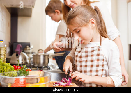 Family cooking background. Mum and daughter cutting onion for salad in the kitchen - Stock Photo