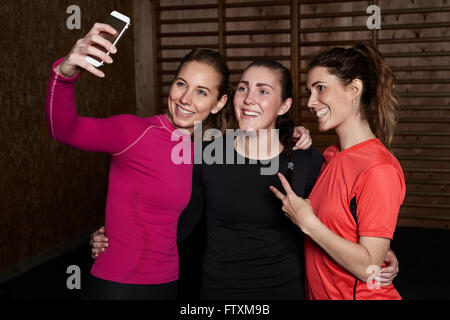 Three young women in gym taking a selfie - Stock Photo