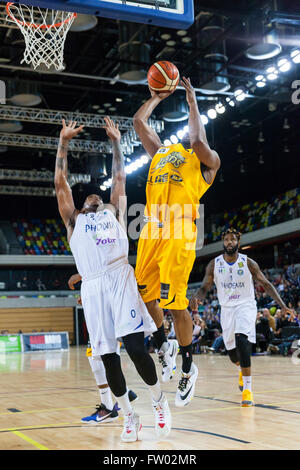 London, UK. 30th March 2016. Lions' Demond Watt (21) jumps up to the basket with the ball, whilst Cheshire's Kinu - Stock Photo
